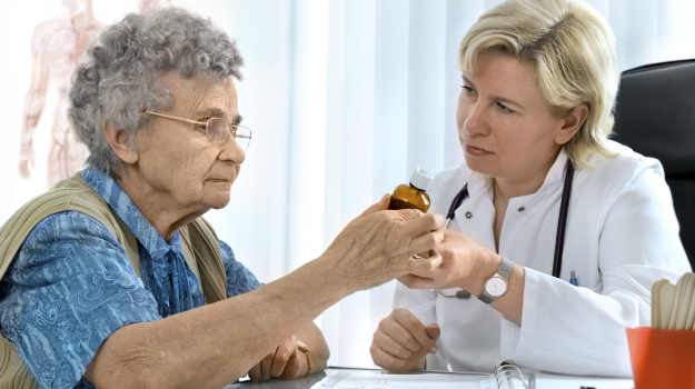 elderly woman getting medication from doctor