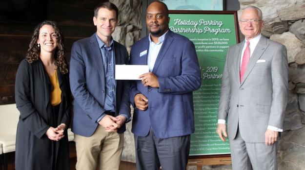 Dan Leroy and Kevin Montgomery accept a donation from The Omni Grove Park Inn